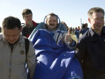 Ground personnel carry Canadian astronaut Chris Hadfield after the Russian Soyuz space capsule landed some 150 km (90 miles) southeast of the town of Zhezkazgan, in central Kazakhstan