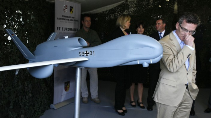 German Defence Minister de Maiziere stands next to model of a Euro Hawk drone at Joint Support Service base in Grafschaft