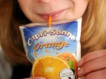Ein Kind trinkt Capri-Sonne