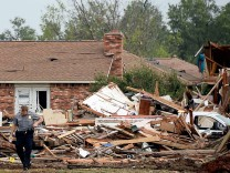 A law enforcement official stands in the yard of a damaged home after a tornado struck Moore