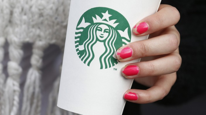 A woman holds a Starbucks takeaway cup in London
