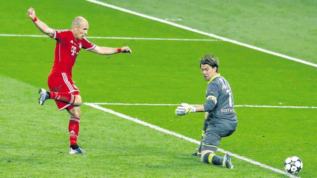 Bayern Munich's Arjen Robben shoots to score past Borussia Dortmund's goalkeeper Roman Weidenfeller during their Champions League Final soccer match at Wembley Stadium in London