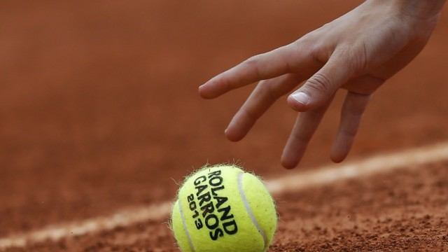 A close up shows a ball boy picking up a tennis ball on Court 7 during the French Open tennis tournament at the Roland Garros stadium in Paris