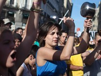 People shout slogans during gathering marking one year anniversary of Spain's Indignados movement in Madrid