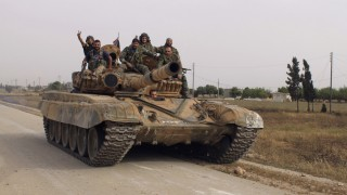 Forces of Syrian President Bashar al Assad are seen on a tank in Qusair village