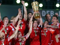 Bayern Munich's Lahm holds up the trophy as he celebrates with his team mates after winning the German soccer cup final match against VfB Stuttgart at the Olympic Stadium in Berlin