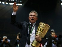 Bayern Munich's coach Heynckes holds the trophy after he was showered with beer as his team celebrates victory over VfB Stuttgart in their German soccer cup (DFB Pokal) final match at the Olympic Stadium in Berlin