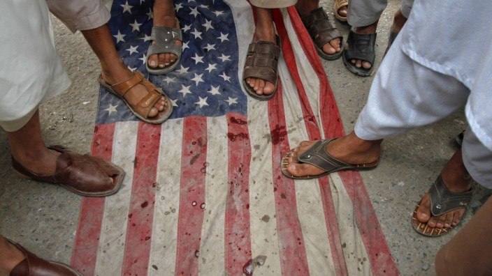 Men step on a U.S flag during an anti-American rally  organized by Shabab-e-Milli, the youth wing of the Jamaat-e-Islami party, in Peshawar