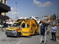 TV crews film near a damaged broadcaster's satellite news network truck at Taksim Square in central Istanbul