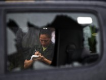 A female soldier is seen through a broken window as she takes notes at the scene of a shootout in Guatemala City