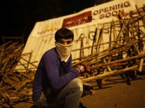 An anti-government protester squats behind barricades during an anti-government protest in Istanbul