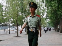 A paramilitary policeman walks near Tiananmen Square in Beijing