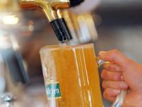 Ein Kellner zapft ein Bier.
