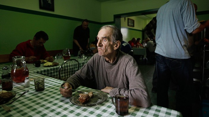 Henryk, who has lived at the Camillian Mission shelter for homeless people for five years, looks out as he eats his meal at the shelter in Warsaw