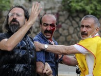 Anti-government protesters ask for help for their wounded fellow after riot police attack them during a protest in Ankara