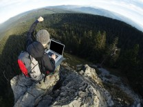 hiker raises arm on cliff's edge while using laptop