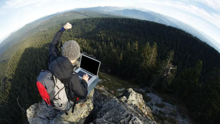 hiker raises arm on cliff's edge while using laptop