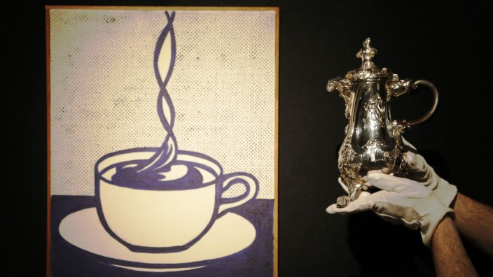 A Christie's employee poses with Roy Lichtenstein's artwork 'Cup of Coffee' and the Lequesne Coffee Pot a George II silver coffee pot with mark of Paul de Lamerie, London 1738,  at Christie's auction house in London
