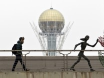 A man walks on a bridge next to a street art installation with the 97-metre monument Baiterek seen in the background in Astana