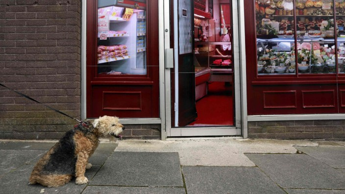 A man walks his dog past a vacant shop, with graphics pasted to the outside to make it look like working butchers shop, in the village of Belcoo, Northern Ireland