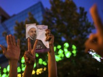 Supporters of moderate cleric Hassan Rohani hold a picture of him as they celebrate his victory in Iran's presidential election on a pedestrian bridge in Tehran