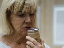 Die Chemikerin Sissel Tolaas analysiert den Duft Münchens, sie riecht an einem Glas.