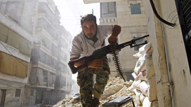 File picture of a Free Syrian Army fighter taking cover during clashes with Syrian Army in the Salaheddine neighbourhood of central Aleppo
