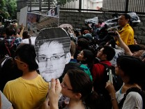 A protester carries a paper cutout of Snowden during a demonstration outside the U.S. Consulate in Hong Kong