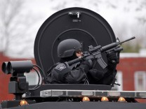 A member of the SWAT team trains a gun on an apartment building during a search for the remaining suspect in the Boston Marathon bombings in Watertown