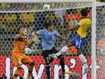 Brazil's Paulinho heads the ball to score a goal past Uruguay's Caceres and goalkeeper Muslera during their Confederations Cup semi-final soccer match at the Estadio Mineirao in Belo Horizonte