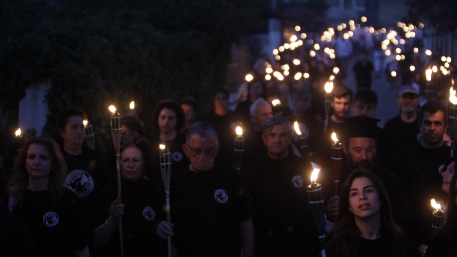 Survivors and relatives of the victims of the Nazi wartime Distomo massacre take part in a torchlight rally in the village of Distomo, northwest of Athens