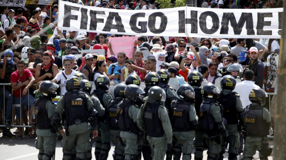 Protesters gather in front of the police during a demonstration near the Estadio Castelao before the Confederations Cup semi-final soccer match between Spain and Italy in Fortaleza