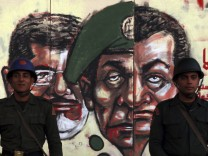 File photo of Republican Guard soldiers standing in front of a mural on the wall of the presidential palace in Cairo