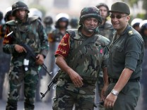 Army soldiers react as they take their positions in front of protesters who are against Egyptian President Mohamed Mursi, near the Republican Guard headquarters in Cairo