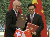 Chinese Commerce Minister Gao shakes hands with Swiss Economy Minister Schneider-Ammann after signing a free-trade agreement in Beijing