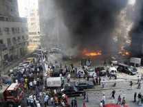 Civil Defence members, security personnel and civilians gather at the site of an explosion in Beirut's southern suburbs
