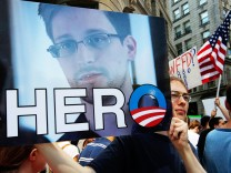 A demonstrator holds a sign with a photograph of former U.S. spy agency NSA contractor Edward Snowden and the word 'HERO' during Fourth of July Independence Day celebrations in Boston