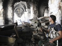 A Free Syrian Army fighter sits on a chair as he holds his weapon inside the Grand Umayyad mosque in Aleppo
