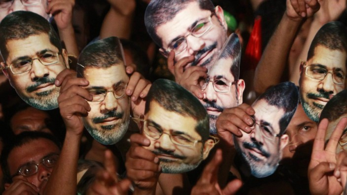 Members of the Muslim Brotherhood and supporters of deposed Egyptian President Mursi hold up masks of him as they gather at the Rabaa Adawiya square, in Cairo