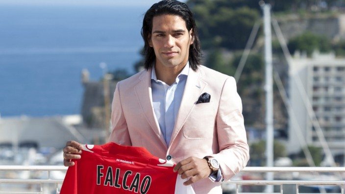 Colombian striker Falcao holds his jersey as he poses after a news conference in Monaco