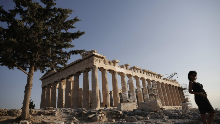 A tourist stands in front of the temple of the Parthenon at the the Acropolis hill in Athens