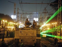 Egyptian Army soldiers sit on an APC on a tram track, during a patrol, as supporters of deposed president Mursi approach the presidential palace in Cair