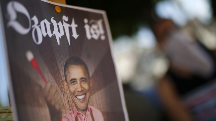 A placard showing U.S. President Obama holding an ethernet cable is seen during demonstration against the NSA in Griesheim