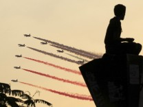 A man is silhouetted as Egyptian military jets fly in formation over Tahrir square in Cairo