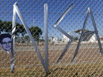 Letters 'NSA' and a mask of Snowden are taped on a fence during a demonstration against the NSA in Griesheim