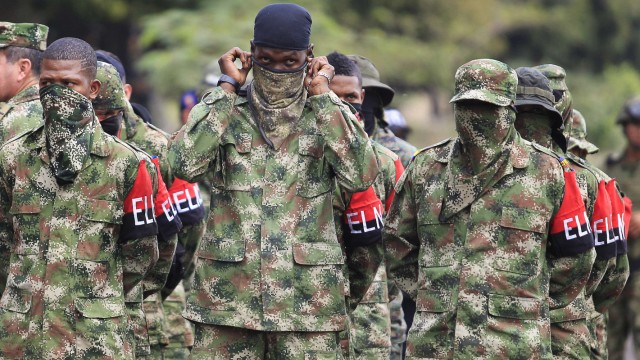 A defected guerrilla group ELN member falls in with comrades after their surrender in Cali