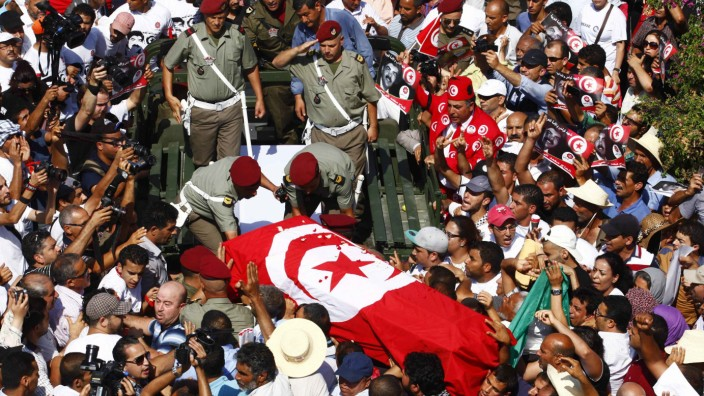 Mourners carry the coffin of slain opposition leader Brahmi during his funeral procession towards a cemetery in Tunis