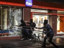 Demonstranten zerstören die Fensterscheibe einer Bankfiliale in São Paolo.