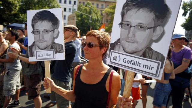 A protester carry two portraits of Snowden during a demonstration against secret monitoring programmes PRISM, TEMPORA, INDECT and showing solidarity with whistleblowers Snowden, Manning and others in Berlin