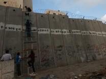 Palästinenser klettern mit einer Leiter über eine Mauer, um aus einem Vorort Jerusalems zur in der Altstadt gelegenen Al-Aksa-Moschee zu kommen.